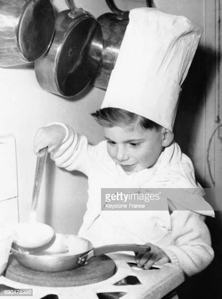 un petit garçon coiffé d'une toque de cuisinier verse la pâte à crêpes dans une poêle à l'aide d'une louche le 1er février 1960