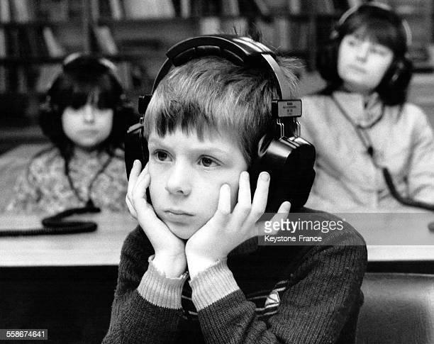 Un petit garçon écoute une cassette grâce à un casque audio dans la nouvelle section audiovisuelle de la bibliothèque Bohnice à Prague République...