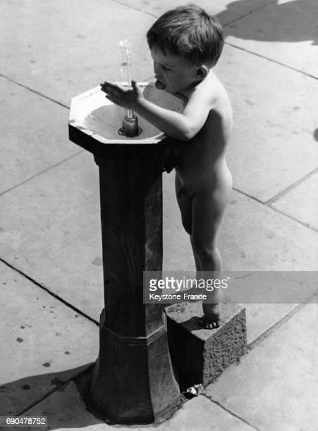 Un petit garçon tout nu boit au robinet d'une fontaine de rue le 27 mai 1937 à Stockholm Suède
