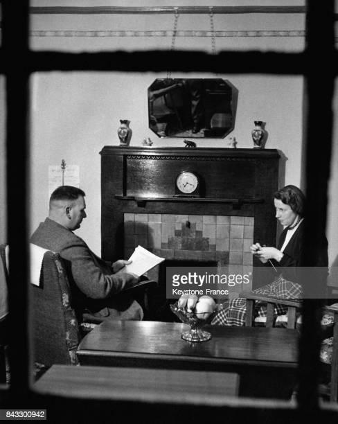 Un policier de retour chez lui lit le journal assis devant la cheminée sa femme à ses côtés tricote à Monmouth Pays de Galles RoyaumeUni en février...