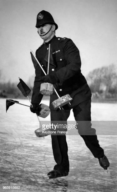 Un policier en patin à glace installe les marques sur la patinoire avant le début du championnat à Cambridge RoyaumeUni le 27 janvier 1933