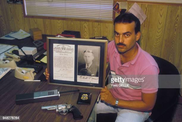 Un policier exhibe une photo de l'agent du Trésor, chef des Incorruptibles, Eliot Ness, juin 1988, Miami, Etats-Unis.