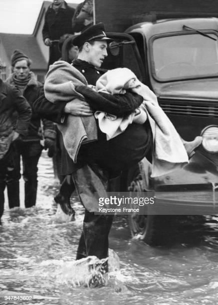 Un pompier porte une vieille dame pour la sauver de l'inondations sur Canvey Island RoyaumeUni le 4 février 1953