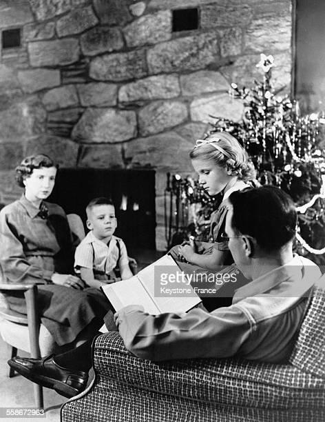 Un père de famille assis dans un fauteuil lit un livre à ses deux enfants et à sa femme rassemblés autour du sapin de Noël