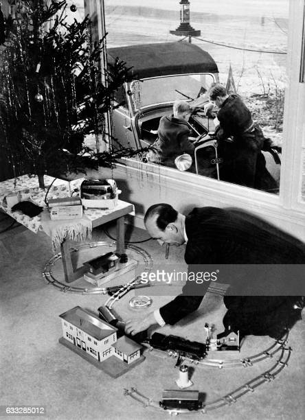 Un père joue avec les jouets de Noël de ses fils qui s'amusent à réparer la voiture de leur père le 25 décembre 1953 / AFP /