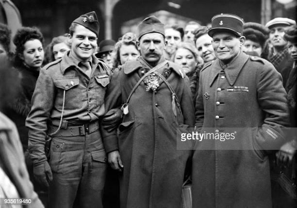 Un prisonnier de guerre rapatrié pose brin de muguet à la boutonnière entre deux militairesdont un soldat de la France libre devant la gare du nord à...