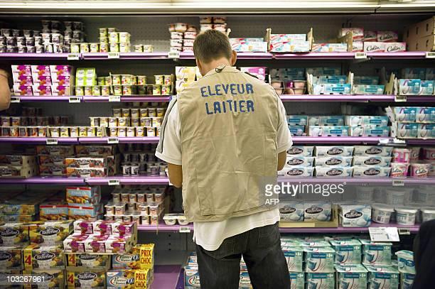 Un producteur de lait s'apprête à réétiqueter les produits laitiers des rayons d'un supermarché le 03 août 2010 à Dijon lors d'une action menée par...