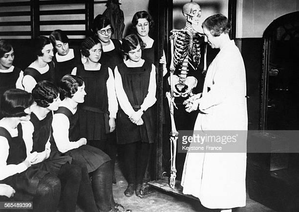 Un professeur de biologie fait un cours à ses élèves féminines en prenant exemple sur un squelette