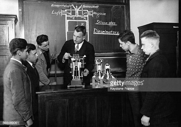 Un professeur fait une démonstration sur un moteur lors d'un cours d'ingénierie devant ses étudiants sous le Troisième Reich à Berlin, Allemagne.
