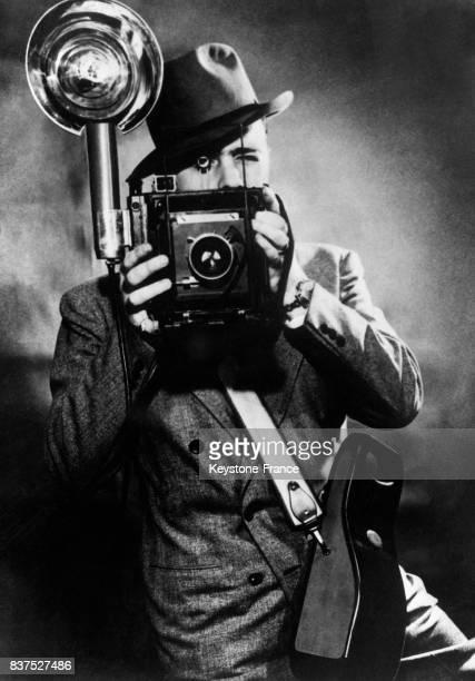 Un reporterphotographe expérimentant le premier appareil à lampe la petite boite suspendue au côté est une sorte d'accumulateur rechargeant...