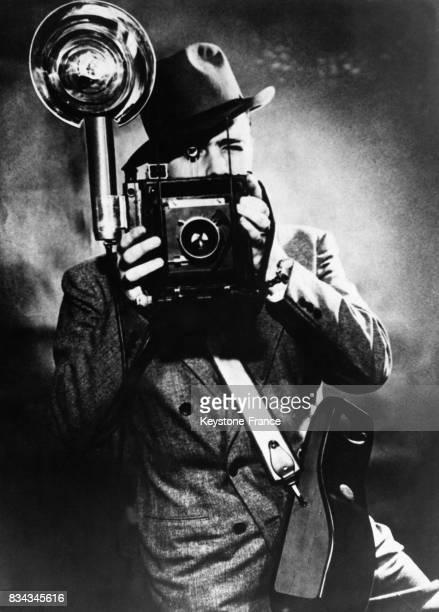 Un reporterphotographe expérimentant le premier appareil photo à lampe nouvelle la petite boite suspendue au côté est une sorte d'accumulateur...