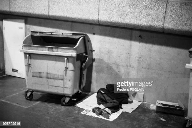 Un sansabri dort près d'une poubelle dans une rue des Paris en octobre 1984 France