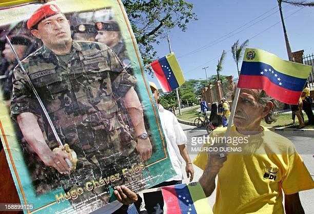 Un simpatizante del presidente de Venezuela, Hugo Chavez, observa un afiche del mandatario durante la visita de Estado que Chavez realiza a Colombia...