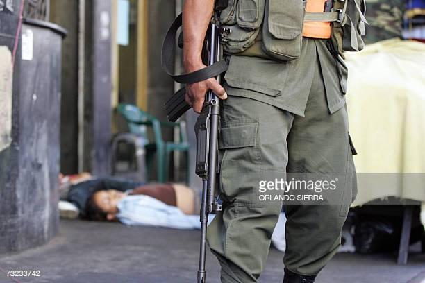 Un soldado del Ejercito custodia la escena del crimen donde fueron acribillados a tiros una pareja de jovenes comerciantes en la sexta avenida o...