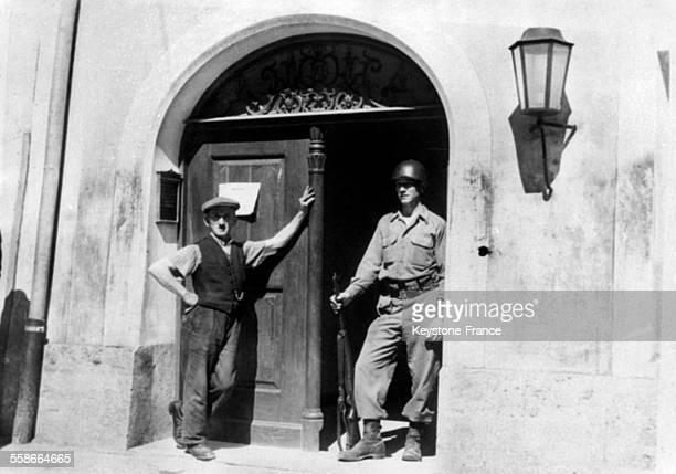 Un soldat américain monte la garde devant la porte cochère de la maison où est né Adolf Hitler à Braunau Autriche circa 1940