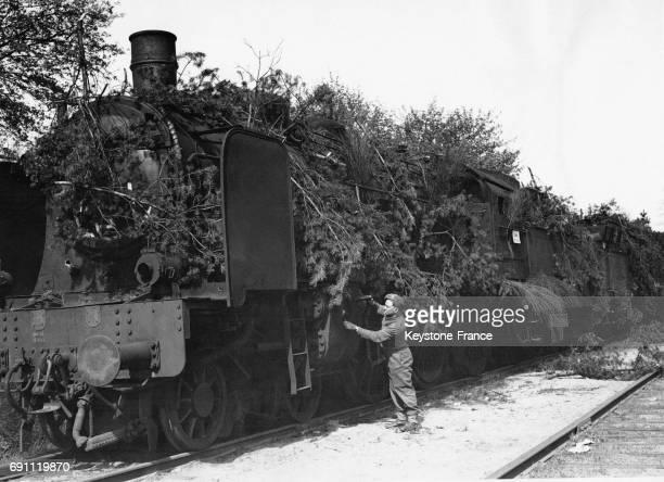Un soldat britannique inspecte une locomotive camouflée puis abandonnée par les Allemands en avril 1945 à Brême Allemagne