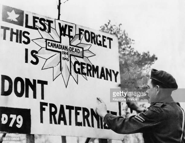 Un soldat canadien affiche un panneau soulignant aux troupes alliées que les Allemands sont des ennemis et qu'il ne faut pas fraterniser 'Lest we...