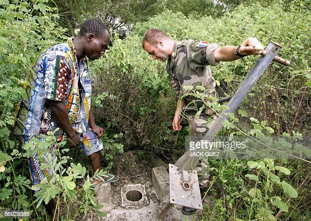 Un soldat Francais de la Force Licorne en Cote d'Ivoire, du 16e bataillon de chasseurs base a Saarbourg en Allemagne, aide, le 27 octobre 2005, des...