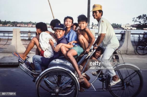 Un tricycle transportant plusieurs personnes en janvier 1991 à HôChiMinhVille Vietnam