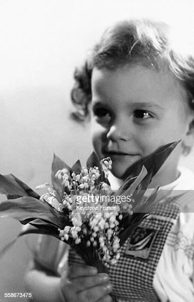 Un très jeune enfant tient à la main un bouquet de muguet le 30 avril 1964