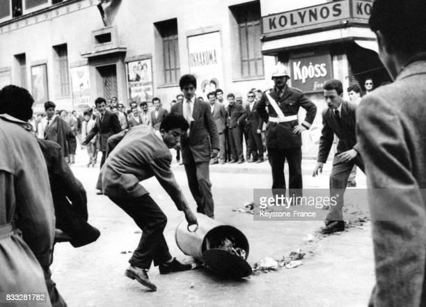 Un étudiant renverse une poubelle sous le regard indifférent d'un policier à Athènes Grèce le 27 mars 1957