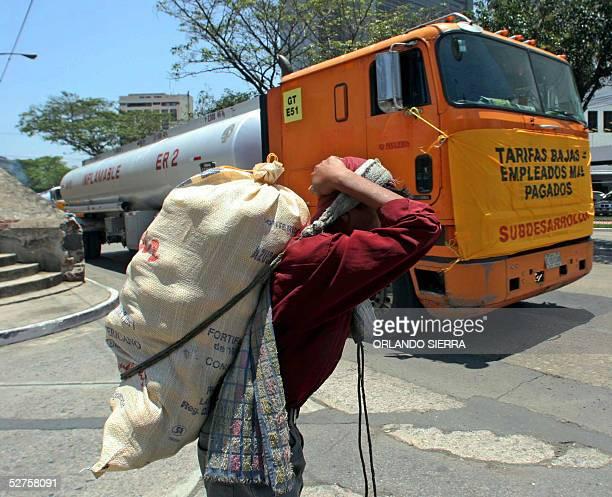 Un vendedor de naranjas pasa junto a uno de los furgones que recorren Ciudad de Guatemala cuyos motoristas le exigen al presidente Oscar Berger un...