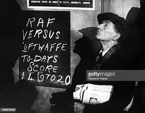 Un vendeur de journaux regardant un combat de chiens durant la bataille d'Angleterre à Londres RoyaumeUni circa 1940