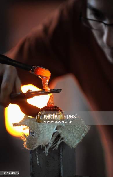 'A MEISENTHAL VERRIERS ET DESIGNERS REINVENTENT LA BOULE DE NOEL' Un verrier fabrique une boule de Noël en verre le 01 décembre 2009 dans l'atelier...