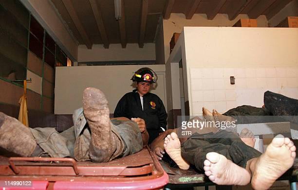 Una agente del Cuerpo de Bomberos Voluntarios observa los cadáveres de seguidores de la socialdemocrata Unidad Nacional de la Esperanza en la morgue...