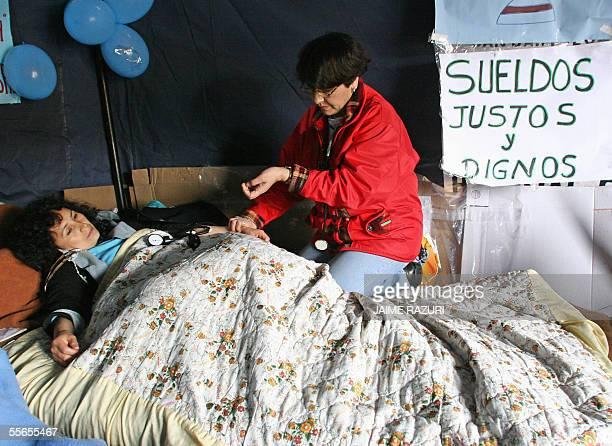 Una enfermera en huelga de hambre es controlada por un colega en una carpa en el atrio de una iglesia en Lima el 16 de setiembre de 2005 en Lima Peru...