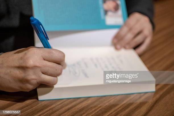 una escritora firma su libro para que sirva de recuerdo a una lectora. - western script stock pictures, royalty-free photos & images