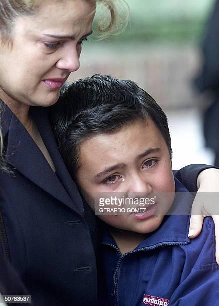 Una madre consuela a su hijo luego de depositar una ofrenda floral a la entrada del colegio Agustiniano Norte en Bogota el 29 de abril de 2004 Un...