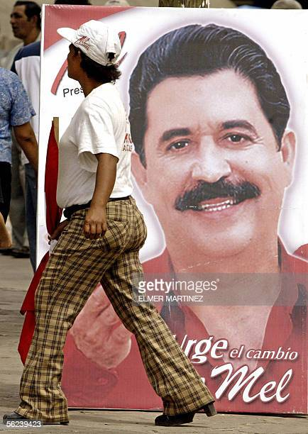 Una mujer camina frente a un cartel de propaganda del candidato presidencial Manuel Zelaya Rosales del Partido Liberal el 19 de noviembre de 2005 en...