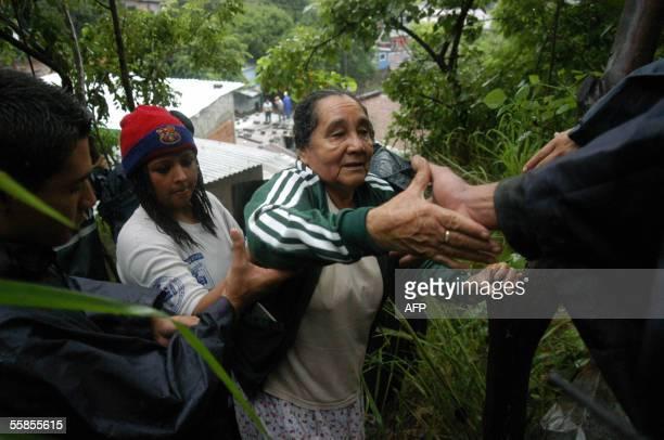 Una mujer es evacuada por comandos de salvamento y agentes de policia el 5 de octubre 2005 ante el desbordamiento de un rio que afecto las casas de...