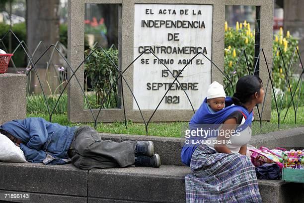 Una mujer indigena con su hijo en la espalda observa los desfiles desde la esquina donde se firmo el acta de independencia de Centroamerica en 1821,...