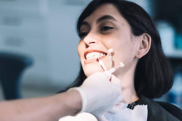 Una mujer joven está siendo tratada por un dentista. El dentista está utilizando unas cuantas piezas dentales de un molde para ver cuál se ajusta mejor a los dientes de la paciente.