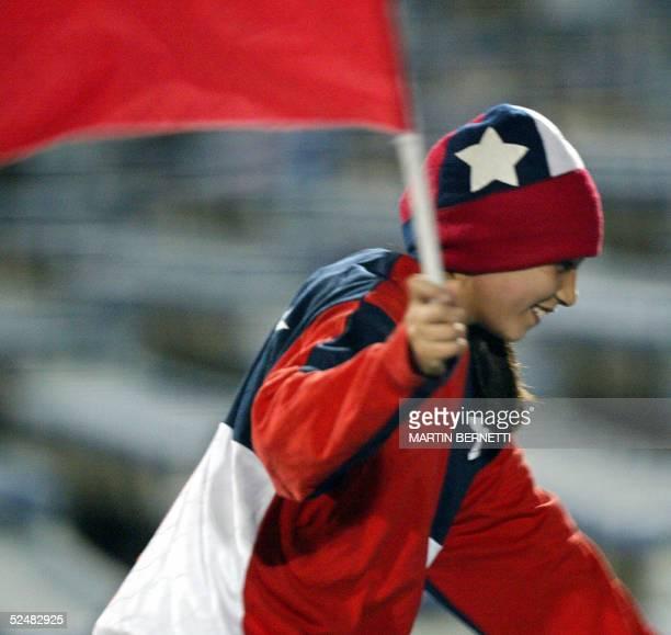 Una nina corre por el estadio con una bandera chilena antes del comienzo del partido frente a Uruguay de la 12a fecha de las eliminatorias...