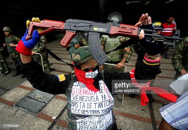 Una opositora al presidente de Venezuela Hugo Chavez carga un fusil Kalashnikov de juguete durante una manifestacion en contra del Consejo Nacional...