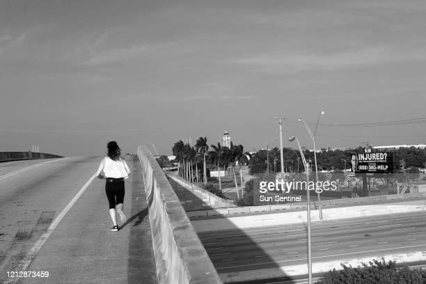 Una persona en una tarde solitaria corre en el paso elevado desde Ravenswood Road hasta el aeropuerto de Fort Lauderdale el 13 de abril de 2020 A...