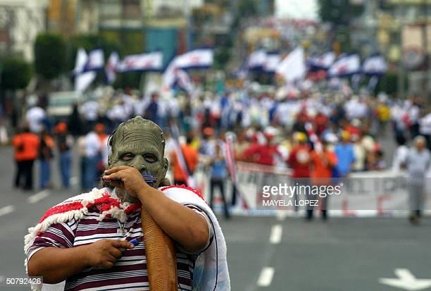 Una persona enmascarada toca un instrumento el 1ro de mayo de 2004 en San Jose cuando encabeza la marcha que miles de trabajadores realizaron para...
