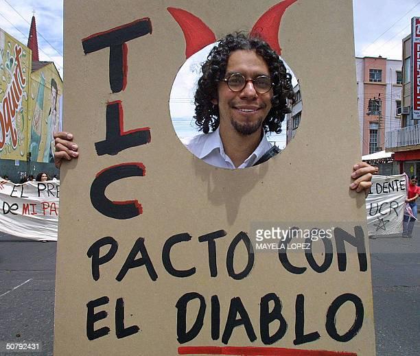 Una persona lleva un cartel contra el Tratadao de Libre Comercio el 1ro de mayo de 2004 en San Jose cuando encabeza la marcha que miles de...