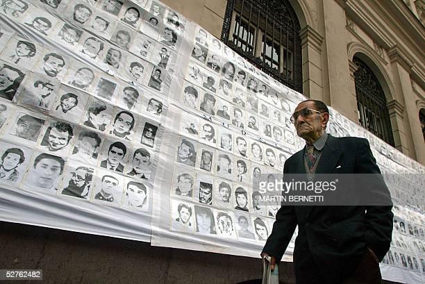 Una persona pasa frente a fotos de desaparecidos durante la dictadura de Augusto Pinochet colgadas frente al palacio de Tribunales en Santiago el 05...