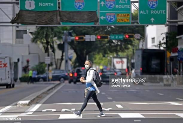 Una persona usando máscara cruza una calle en el downtown de Miami el 18 de marzo