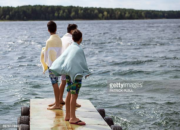Unaccompanied minor refugees from Syria and Afghanistan stand on a bridge at the Helenesee lake near Frankfurt an der Oder eastern Germany after...