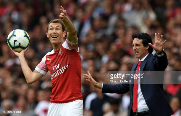 Unai Emery Manager of Arsenal gestures as Stephan Lichtsteiner of Arsenal prepares to take a throw during the Premier League match between Arsenal FC...