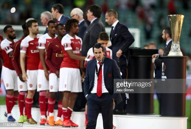 Unai Emery Manager of Arsenal looks dejected as he walks past the Europa League Trophy after collecting his runners up medal following his team's...