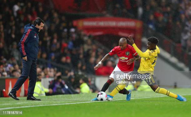 Unai Emery Manager of Arsenal looks on as Ashley Young of Manchester United battles for possession with Bukayo Saka of Arsenal during the Premier...