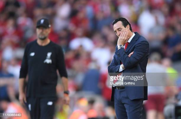 Unai Emery Manager of Arsenal looks on in front of Jurgen Klopp of Liverpool during the Premier League match between Liverpool FC and Arsenal FC at...