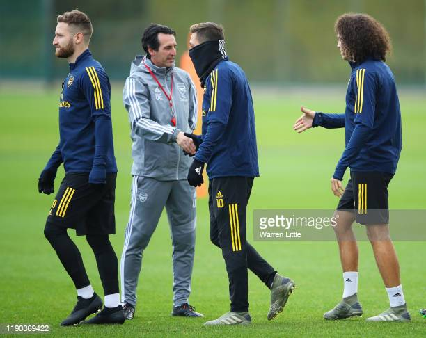Unai Emery Manager of Arsenal shakes hands with Mesut Ozil and team mates Shkodran Mustafi and Matteo Guendouzi during an Arsenal training session on...