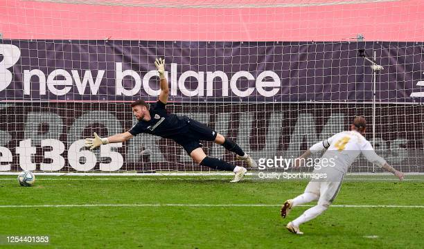 Unai Simon of Athletic Club tries to save the penalty struck by Sergio Ramos of Real Madrid CF during the Liga match between Athletic Club and Real...